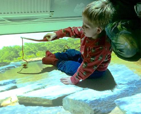 Noah Wall playing in his sensory room on interactive floor
